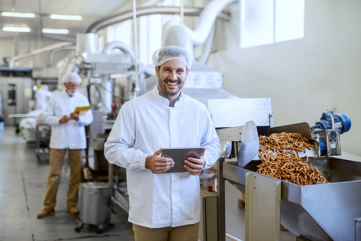 Young smiling manager in sterile uniform holding tablet and looking at camera while standing in a manufacturing food factory.